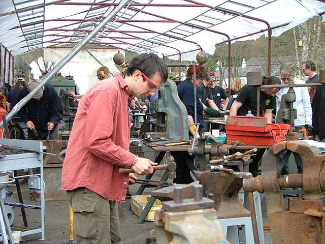 Blacksmiths working on their designs at the Forge In event at Kielder Castle.